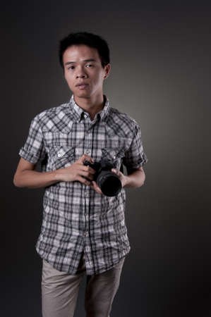 A young Asian man holding a SLR camera Stock Photo