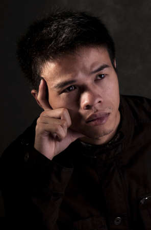 Young Chinese Man seriously thinking about the future