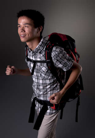 Asian man excited about hiking in the outdoors wearing backpack Stock Photo
