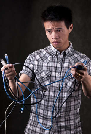 Asian Man holding computer cables looking very confused and frustrated Stock Photo