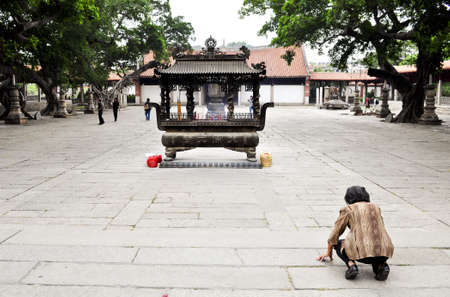 Quanzhou, China - October 07:  An old woman prays to a small shrine at a famous temple in Quanzhou, China on October 7, 2010. Editorial