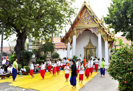 Bangkok, Thailand - December 19:  Some students with teachers learning Thai dancing outside of a famous temple in Bangkok on December 19, 2010