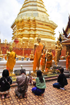 Chiang Mai, Thailand - December 22:  People praying at a famous buddhist temple in Thailand on December 22, 2010