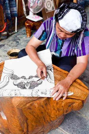 Xijiang, China - July 05:  A traditional woman making a Batik Tapestry in Xijiang, China.  A very traditional technique that is popular among tourists.