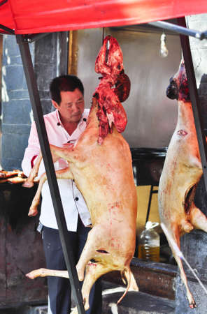 Lijiang, China - July 20:  A Market man butchering and cleaning the goats in the market on July 20, 2011.  A very common site in China. Editorial