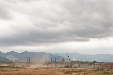 Dust flies with construction in developing Asia with mountains in the background