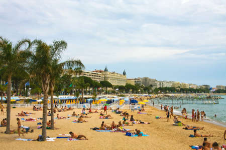 french riviera: CANNES, FRANCE - June 13:  People on a beach about famous hotel Carlton,  2010 Editorial