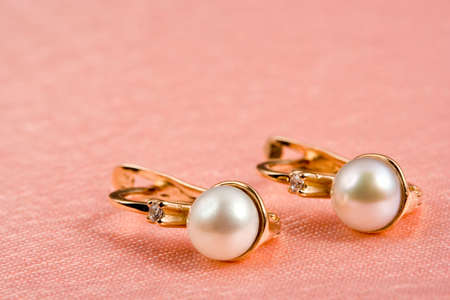 pearl jewelry: Golden pearl jewelry on rosy silk folds. Background for Valentines Day