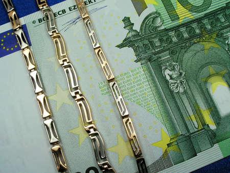 Gold  bracelets on background of euro  photo