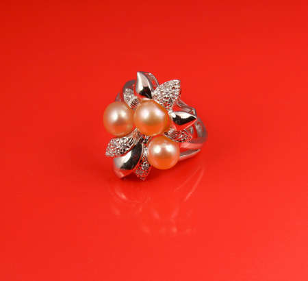 brilliants: Jewelry pearl ring on red