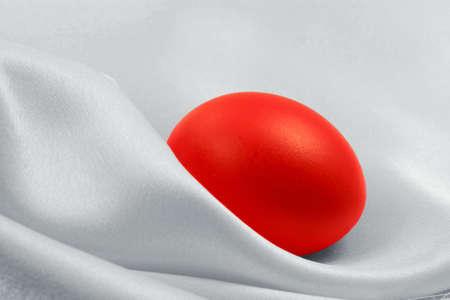 Red egg on white silk background Stock Photo - 2597608