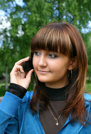 Beautiful young woman on nature with telephone photo