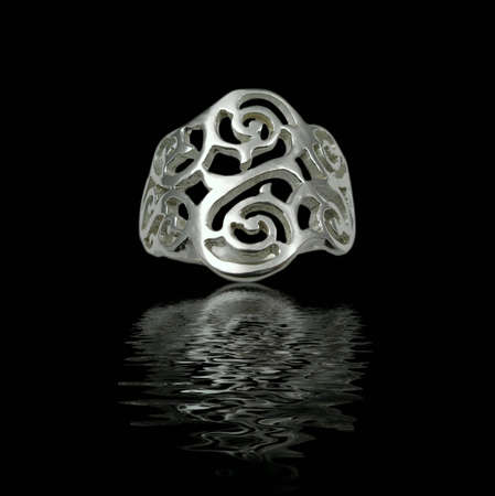 Silver jewelry on black background with water photo