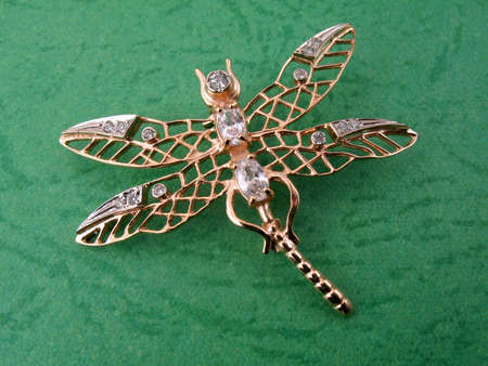 Jewelry dragonfly on a color green background Stock Photo - 4122546