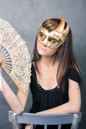 Pretty young woman  in carnival mask with fan  photo