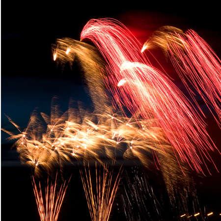 salvoes: Celebratory bright firework in night sky Stock Photo