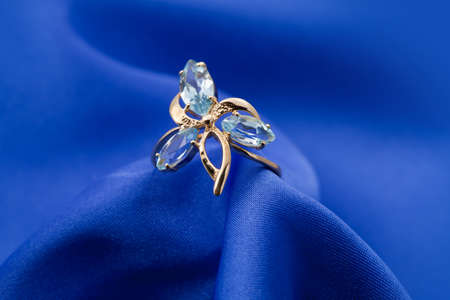 textille:  Elegant jewelry ring with jewel stone on a background of silk Stock Photo