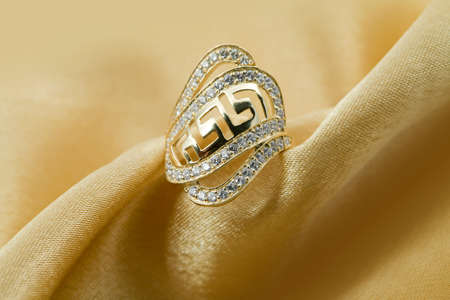Elegant jewelry ring with jewel stone on a background of golden silk Stock Photo - 8637037