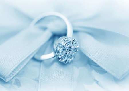 wedding accessories:  Elegant jewelry ring with jewel stone on a background of silky bow  Stock Photo