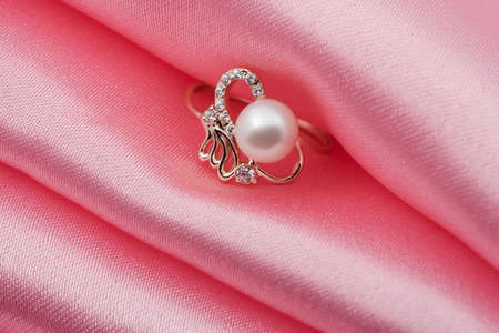 textille:  Elegant jewelry ring with jewel stone on a background of pink silk Stock Photo