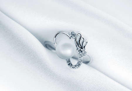 fine silver:  Elegant jewelry ring with jewel stone on a background of silk Stock Photo