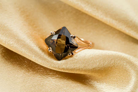 textille:  Elegant jewelry ring with jewel stone on a background of golden silk  Stock Photo