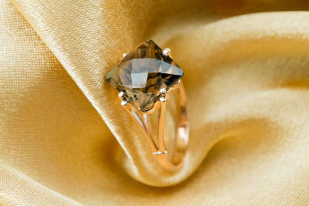 textille:  Elegant jewelry ring with topaz on a background of golden silk