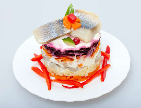 Salad of  fish herring for snack on a plate photo
