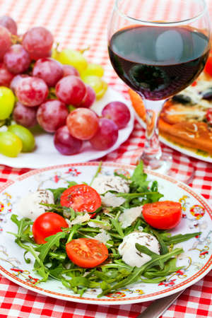 Food - plate with italian  dinner - salad, pizza and vine on a table photo