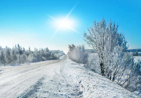 Winter landscape,hoarfrost and snowdrift, road in the country and sunny rays.   Imagens