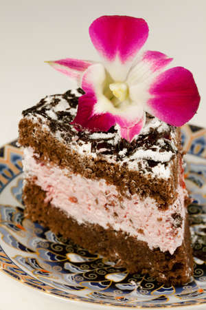 sweetened: Tasty  celebratory fancy cake and flower orchid Stock Photo