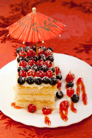 Tasty baked fancy cake decorated Red and black currant    photo