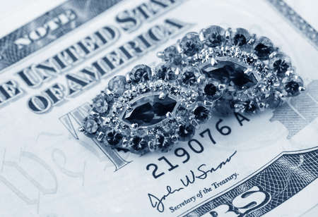 American dollars and jewelry   Bundle of bank notes and brilliant ring Stock Photo - 13208210