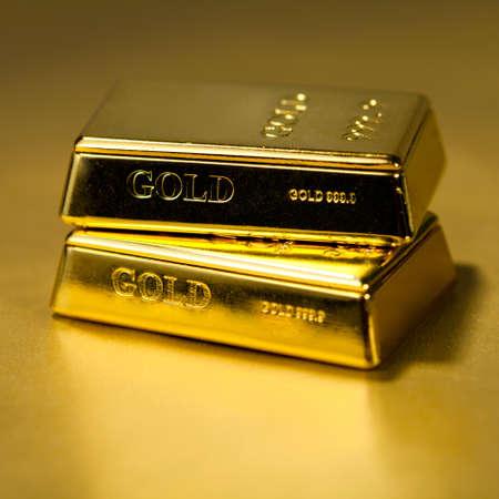 lingotes de oro: Dos lingotes de oro sobre fondo de oro