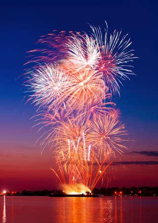 fuegos artificiales: Fuegos artificiales de colores en un cielo de la noche, reflejo en el agua
