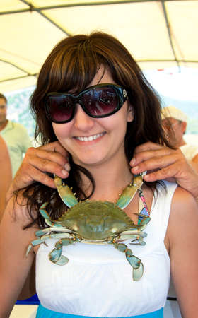 Young happiness woman with necklace of blue crab photo