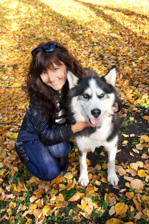 Dog siberian husky and young woman on green grass in a park photo