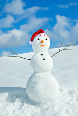 Snow man in santa cap on nature in sunny cold day Stock Photo