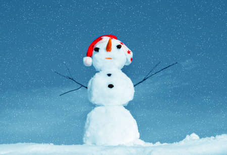 Snow man in santa cap on nature in sunny cold day photo