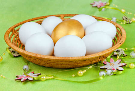 White and one golden  Eggs in the basket for holiday Easter  photo