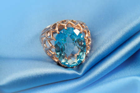 jewelle: Golden jewelry ring with blue topaz on blue background Stock Photo