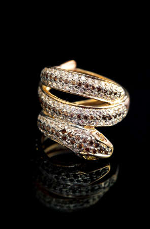 Golden jewelry accessories - ring serpent with brilliants on black background photo
