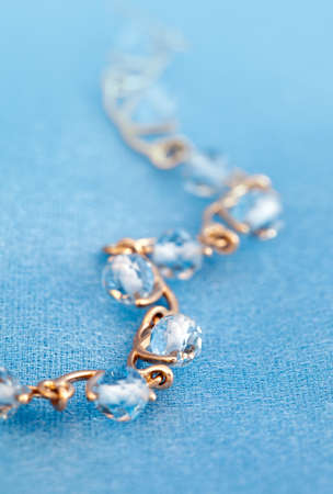 jewelle: Golden jewelry  bracelet with blue topaz on blue background Stock Photo