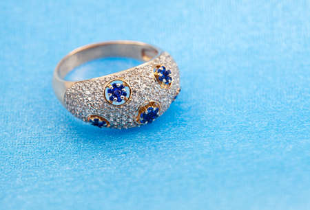magnificence: Golden jewelry ring with sapphires and brilliants on blue background