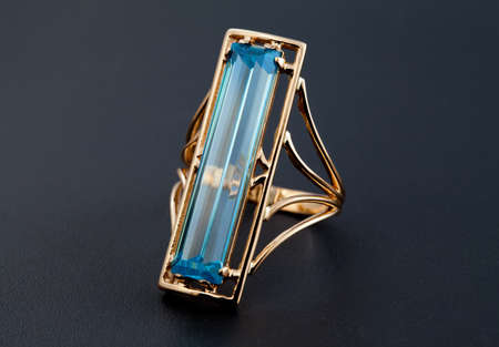 jewelle: Golden jewelry accessories   with blue topaz on black background
