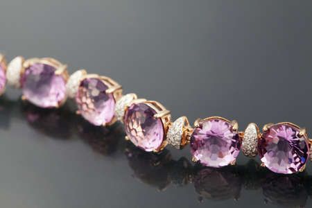 jewelle: Golden jewelry accessories - bracelet with amethyst with brilliants on grey background Stock Photo