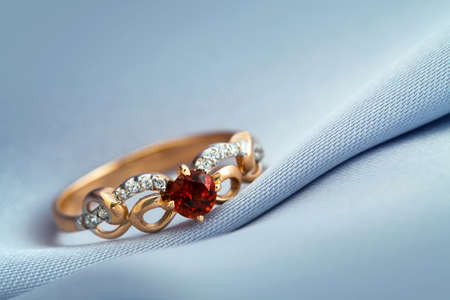 magnificence: Golden jewelry accessories - ring with ruby on grey background