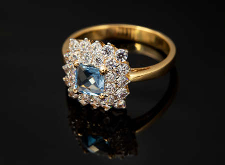 brilliants: Golden jewelry ring with sapphire and brilliants on black background Stock Photo