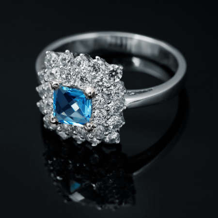 Jewelry ring with sapphire and brilliants on black background photo
