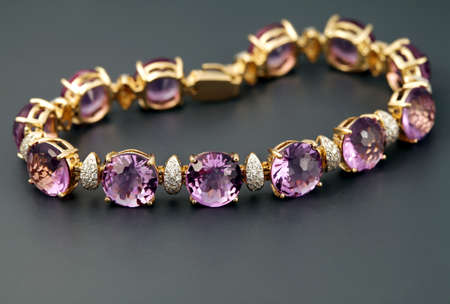 Golden jewelry  bracelet with amethysts  and brilliants on grey  background photo